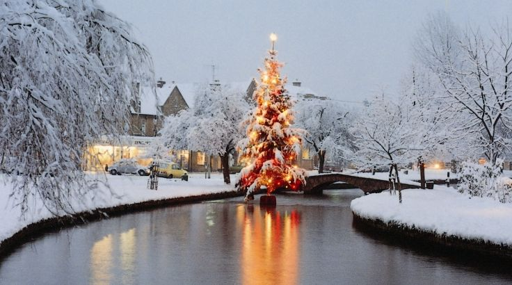 A snow-covered Christmas tree in a river in the middle of a picturesque Cotswold village with fairy lights reflecting on the water. Does it get any more Christmassy than this?