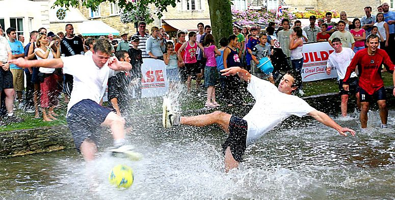 """Players from Bourton Rovers FC take part in their annual August Bank Holiday derby fixture in the River Windrush where the """"pitch"""" is always guaranteed to be waterlogged. Picture courtesy Cotswolds Conservation Board."""