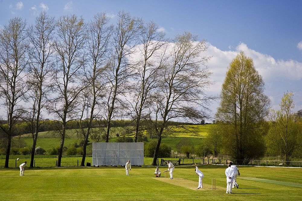 A classic Cotswold cricket scene with a village match being played at Swinbrook, near Chipping Norton. Copyright Tim Graham. www.timgrahamstock.photoshelter.com/gallery/Cotswolds/