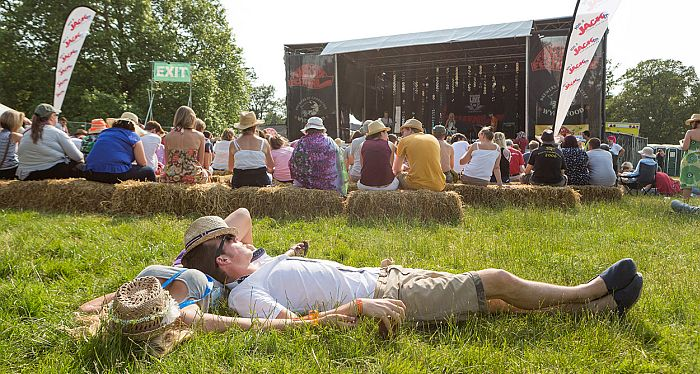 Chilled-out festival goers enjoying the entertainment on the Riverside Stage.