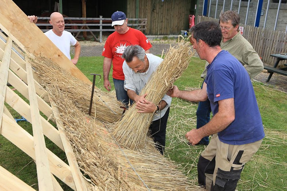 Trainees in the Cotswolds learning the art of thatching, a rural skill that takes years to master. Picture © Cotswolds Conservation Board