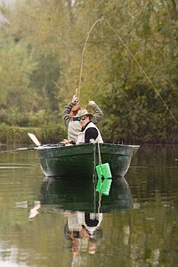 Two men and a boat: Casting a line at a fishing lake in the Cotswolds.
