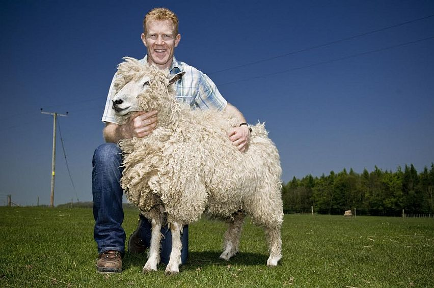 Cotswold farmer and TV presenter Adam Henson with a Cotswold Lion sheep.