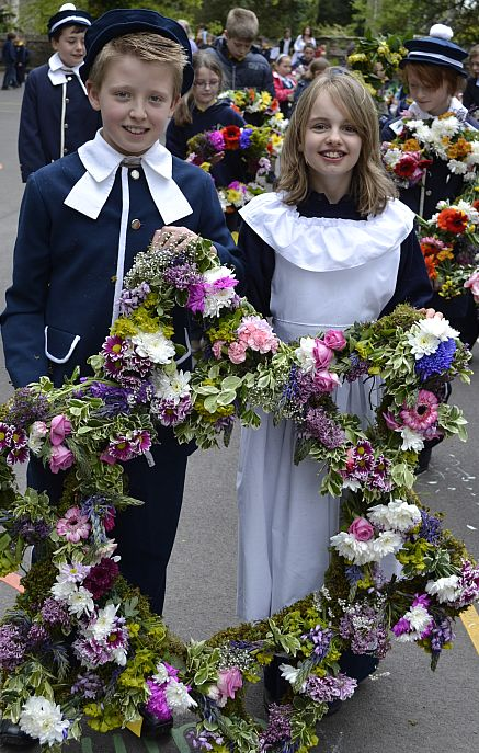 Children carrying star-shaped floral arrangements head the procession of flowers.