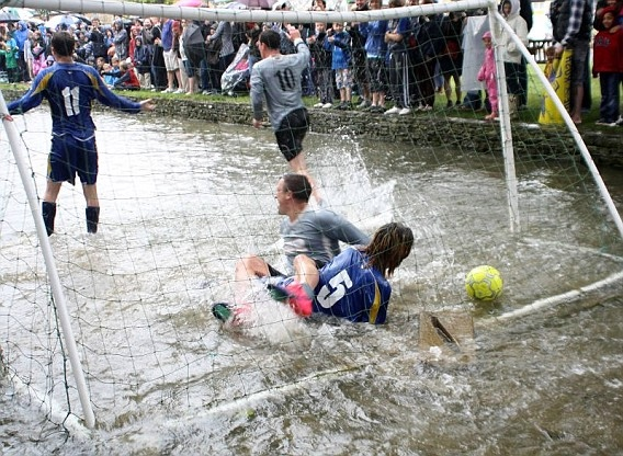 Football in the river at Bourton-on-the-Water is among the quirky sports that take place in Gloucestershire.