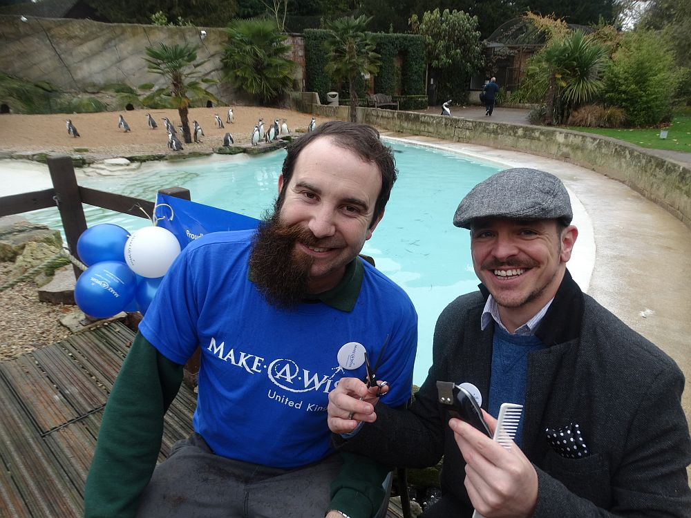 A half-shaven Chris Green with barber Michael in front of the penguins. Picture: Cotswold Wildlife Park.